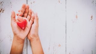 Hands holding a small heart.