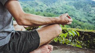 Man meditating on a mountain.