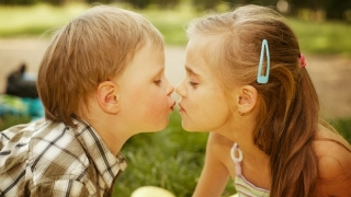 A young boy and girl kissing
