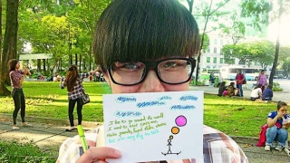 Boy with glasses holding up note and drawing.