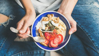 Woman eating bowl of granola.