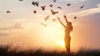 Woman holding her arms up and birds flying in night sky