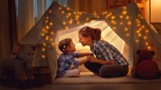 Mom and daughter in a tent indoors.