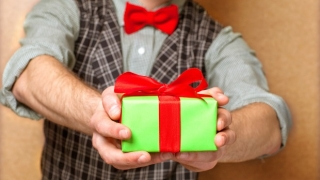 Man holding out a small wrapped present.