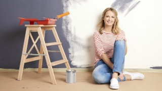 Woman painting walls of her home.