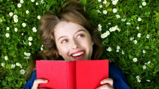 Woman on grass reading a book