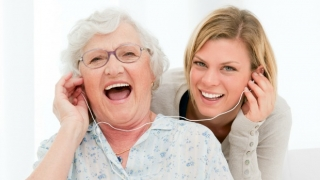 Two women listening to music on earphones