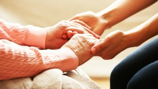 Younger woman holding older woman's hands.