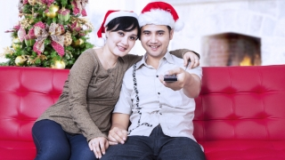 Happy christmas couple wearing santa's hats and holding a remote control