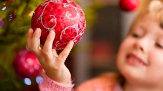Little girl holding Christmas ornament.