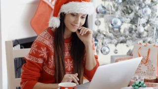 Woman sitting at a desk working on laptop with Christmas decor.