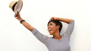 Energetic woman holding up her hat.
