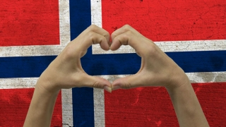 The Norwegian flag with hands in a heart-shape in front of it.