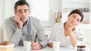 Married couple having breakfast and looking bored.