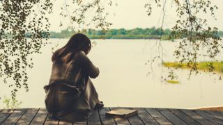 Depressed woman by a lake.