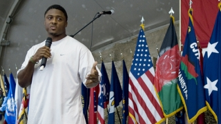 Warrick Dunn talking in front of flags
