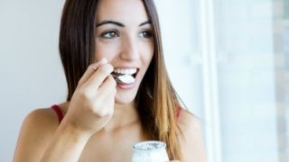 Woman eating spoonful of yogurt.