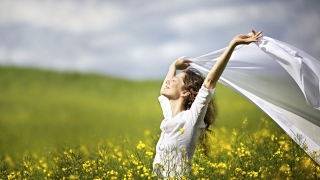 A happy young woman is standing in a field of yellow flowers with her face to the sun.