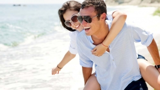 Smiling man giving a woman a piggyback ride on a beach