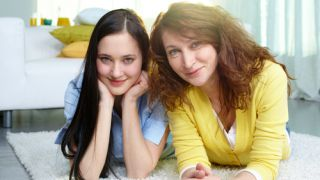 Restful mother and teen-age daughter lying on the floor at home, self-esteem