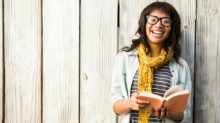Young woman holding a book and smiling.