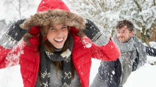Couple having a fun snowball fight.