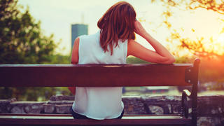 Pensive woman sitting on a bench.