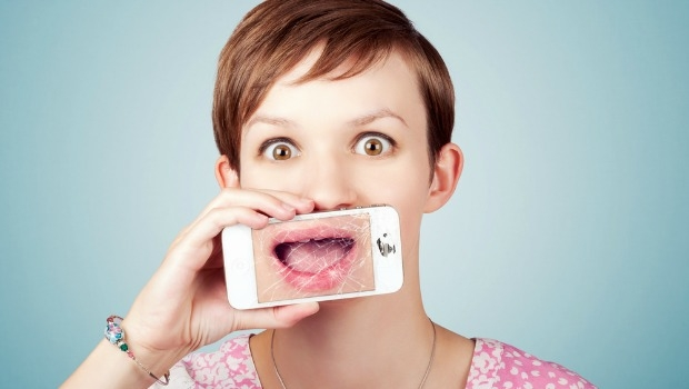 Woman with iphone covering her mouth