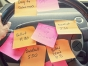Many post-its on a steering wheel.