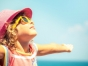 Little girl in hat and sunglasses on the beach