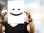 Woman holding paper with happy face.