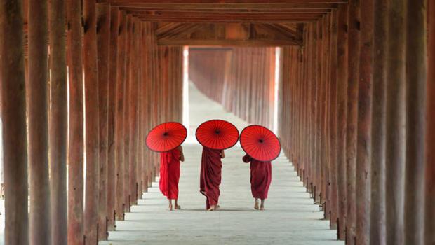 Buddhist monks walking down a corridor.
