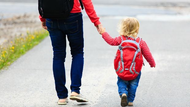 A parent and child walk to school