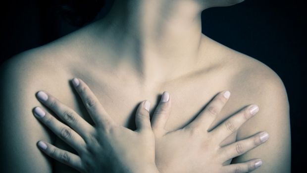 Image of woman embracing her chest.