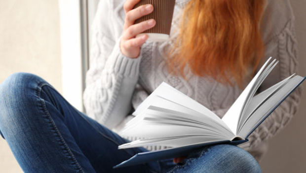 Red-haired woman reading a book.