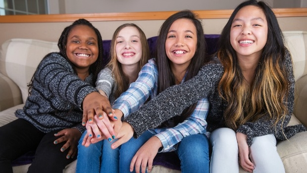 Diverse group of teen girls sitting on a couch touching hands.