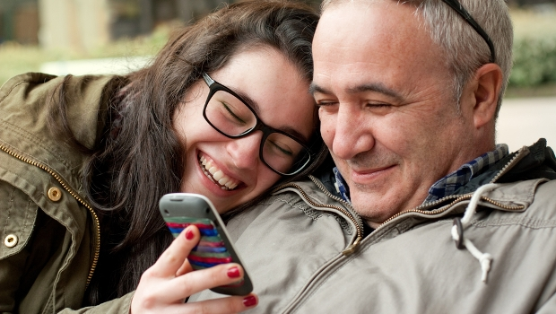 Father and daughter look at phone smiling and happy