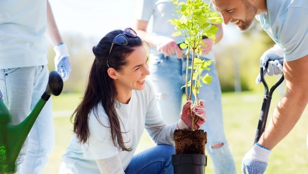 Woman volunteering in a garden with a group of people.