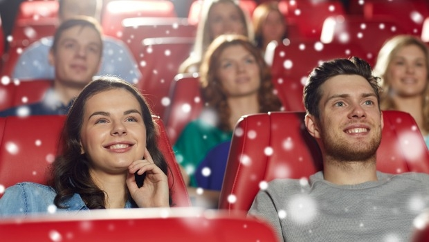 Young couple watching a movie in theater.