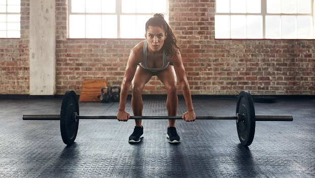 Woman lifting a heavy weight in a gym.