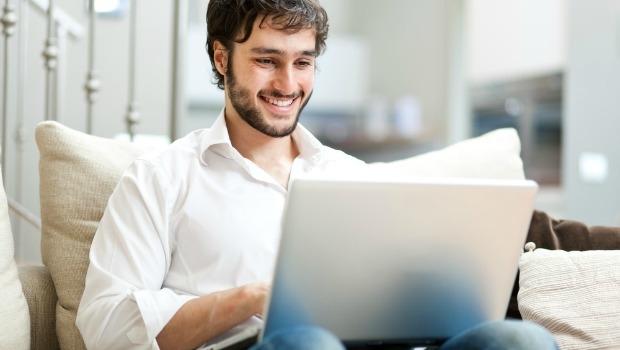 Attractive bearded man checks his social media on a laptop computer.