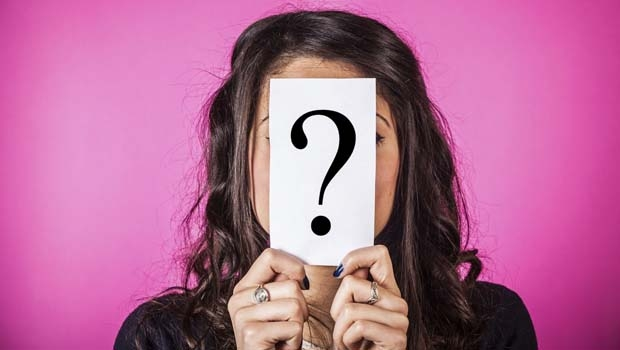 Woman holding a piece of paper with a question mark over her face.