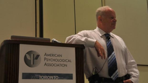 Martin Seligman leans on podium