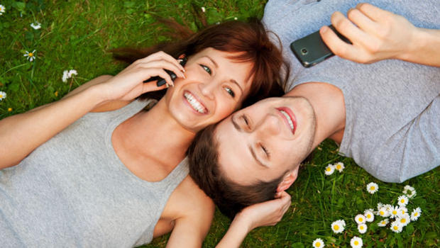 Couple lying on grass with phones.