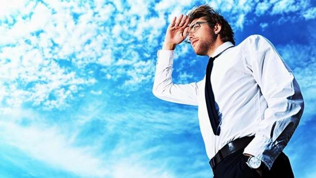 Businessman standing looking upward