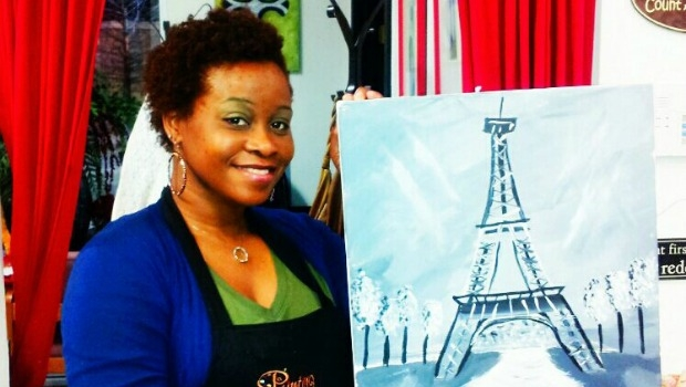 Woman holding up a painting of the Eiffel Tower