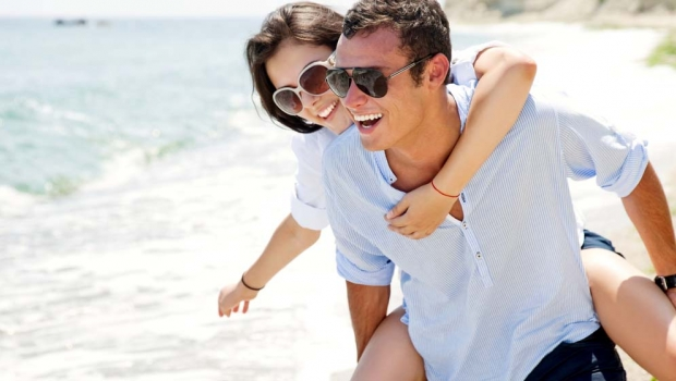 Smiling man giving a woman a piggyback ride on a beach