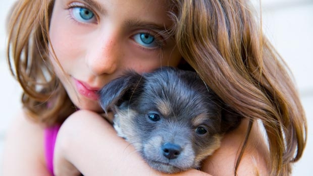 Girl hugging her puppy