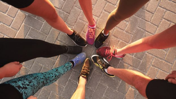 Runners touching sneakers as a group