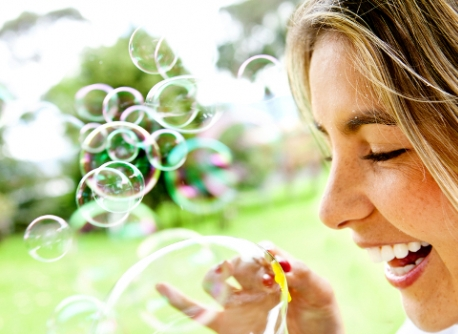 Happy woman portrait blowing soap bubbles at the park.
